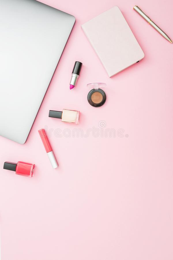 Home feminine desk workspace with laptop, notebook and cosmetics on pink background. Top view. Flat lay lifestyle concept. royalty free stock image