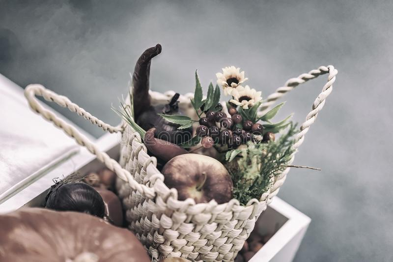 Home festive flower arrangement from leaves, flowers, vegetables, fruits, berries in the rustic wicker basket. Autumn stock images