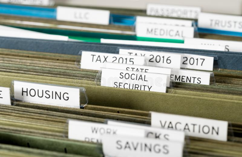 Home filing system for Social Security organized in folders. Close up of a well organized home filing system with tabs for each subject with focus on social stock image