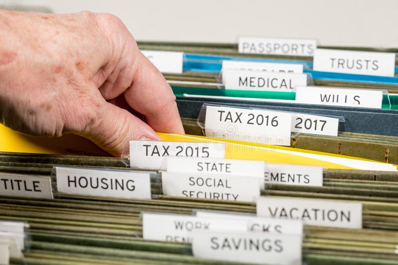 Home filing system for taxes organized in folders. Close up of a well organized home filing system with tabs for each subject and focus on tax return papers royalty free stock photos