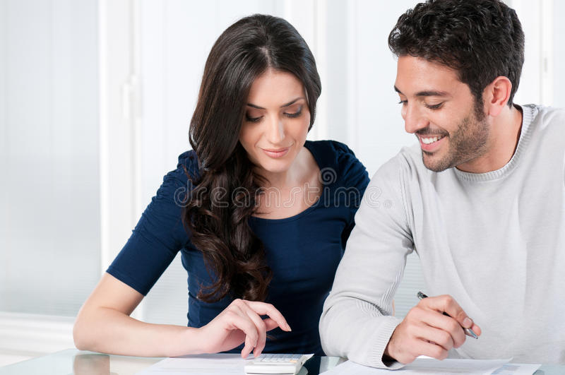 Home finance. Happy smiling couple calculating their financial investments at home