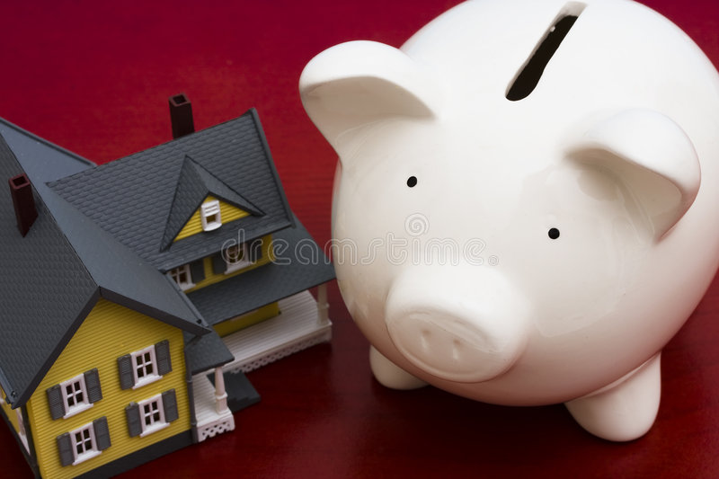 Home Finances. Home with piggy bank on a red background stock images