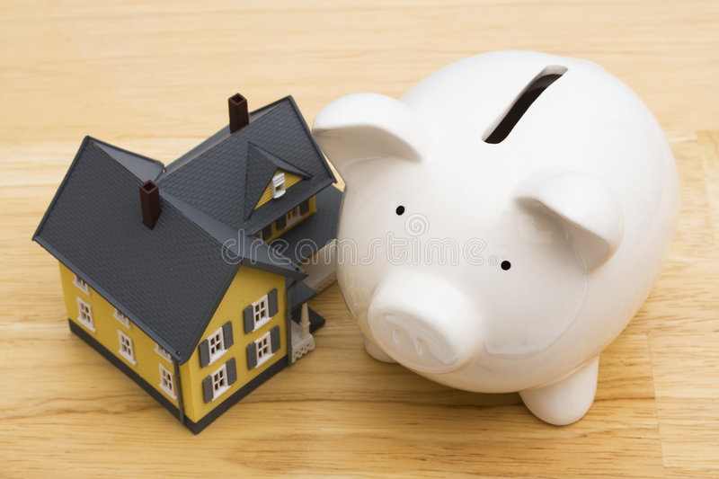 Home Finances. Close up of a home with a piggy bank royalty free stock photos
