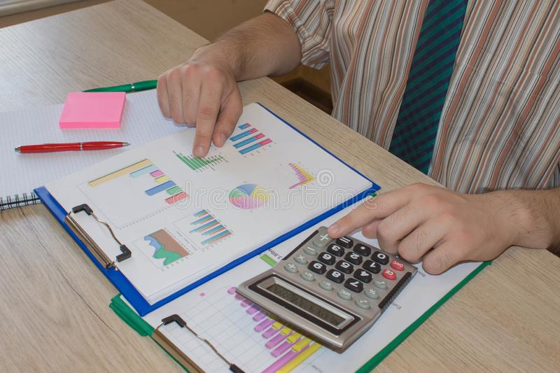 Home finances, investment, economy, saving money or insurance concept. Male working with calculator and document. Home finances, investment, economy, saving royalty free stock photography