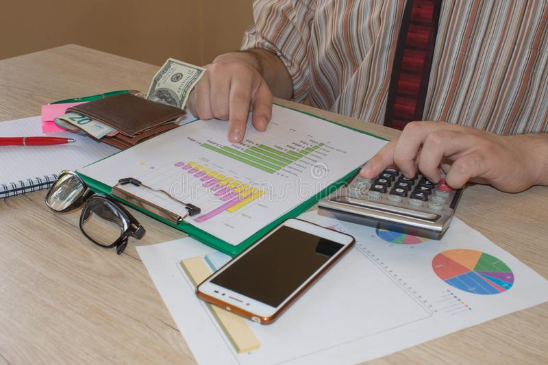 Home finances, investment, economy, saving money or insurance concept. Male working with calculator and document. Home finances, investment, economy, saving stock image