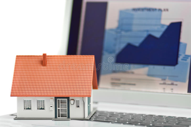 Home financing. Model house in front of computer with financing plan - mortgaging or home financing concept royalty free stock photos