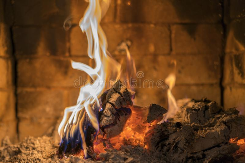 Home fireplace with beautiful orange fire and wood fire close. Burning fire in the fireplace. Logs on fire stock image