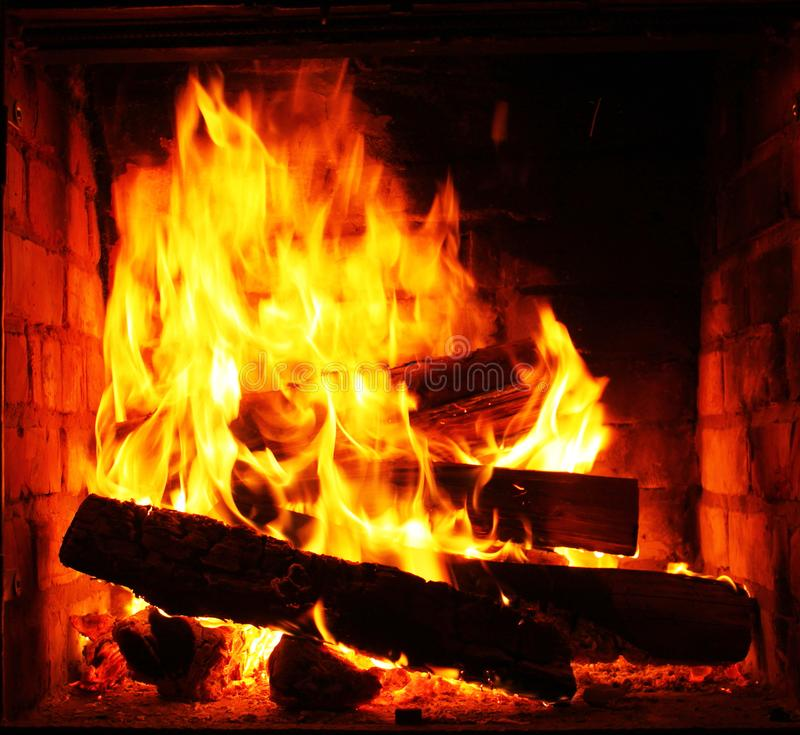 Home fireplace with beautiful orange fire and wood fire close-up. As home comfort and hearth royalty free stock photos