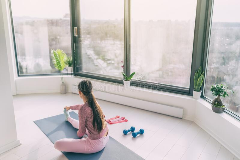 Home fitness yoga workout woman exercising at home stretching legs warm up training. Fit girl working out in morning. Sunlight in living room of apartment house royalty free stock photo