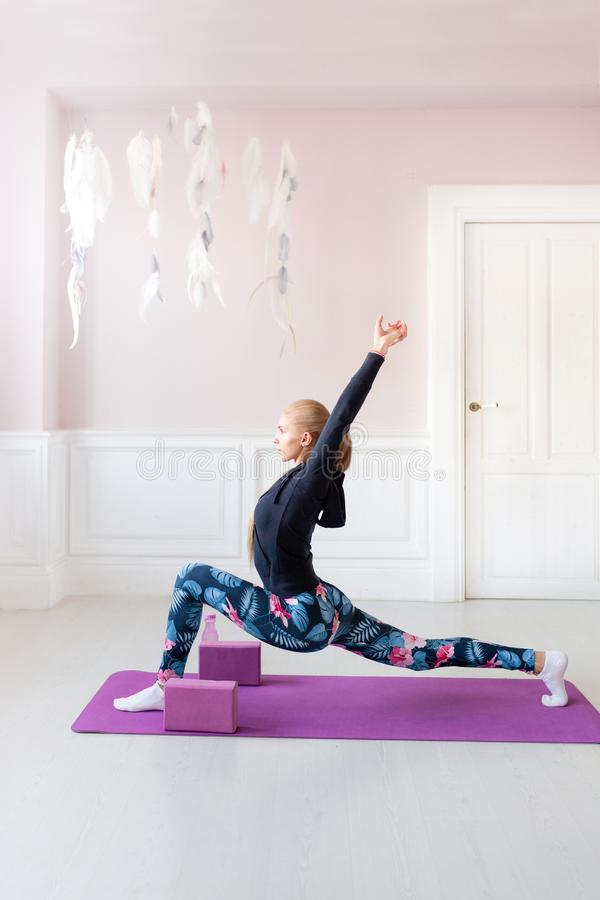Home fitness. Young woman warming up before training doing exercises to stretch her muscles and joints. Lovely young. Young woman warming up before training royalty free stock image