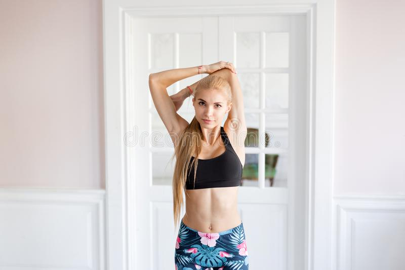 Home fitness. Young woman warming up before training doing exercises to stretch her muscles and joints. Lovely young. Young woman warming up before training stock images