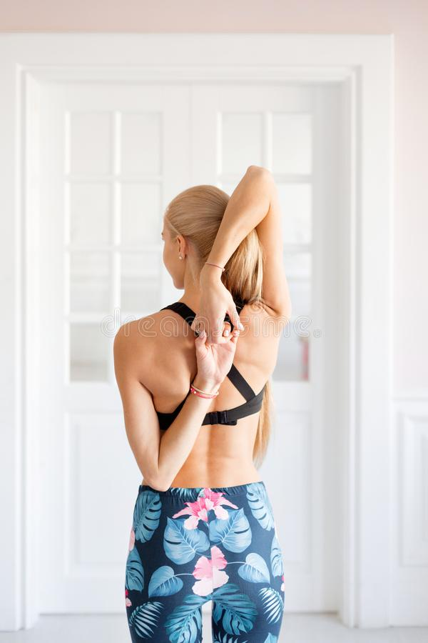 Home fitness. Young woman warming up before training doing exercises to stretch her muscles and joints. Young woman warming up before training doing exercises to stock photo