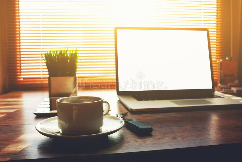 Home freelance desktop with open laptop computer. Cup of coffee, digital tablet and green plant lying on the table, business person net-book with blank screen royalty free stock photography