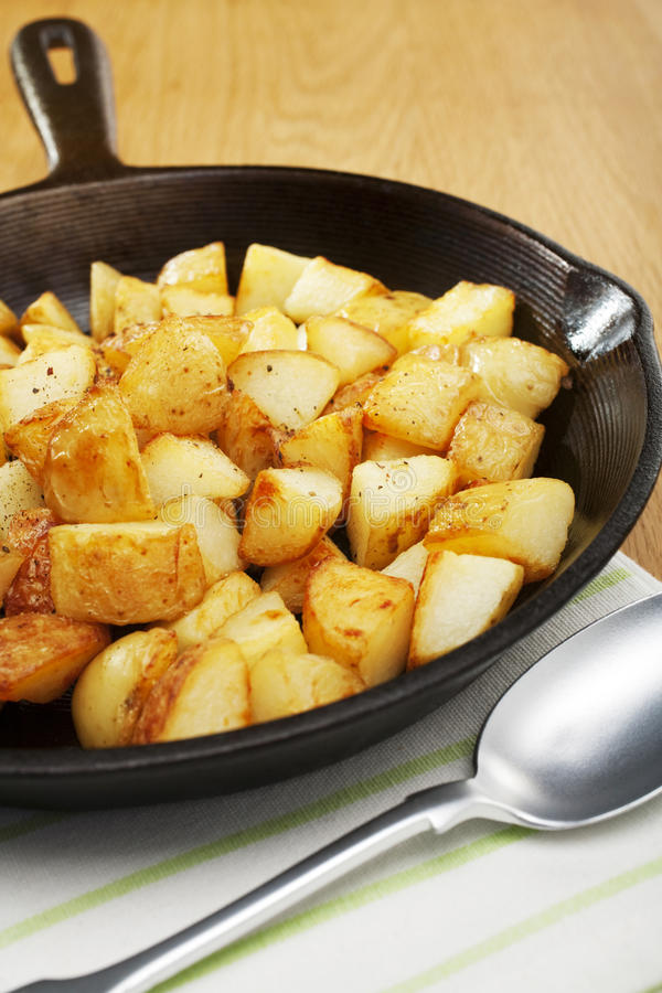 Home Fries. A skillet or frying pan containing home fries or saute potatoes stock photo