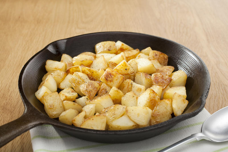 Home Fries or Saute Potatoes in a Skillet. A small cast iron skillet or frying pan filled with home fries or saute potatoes stock photo