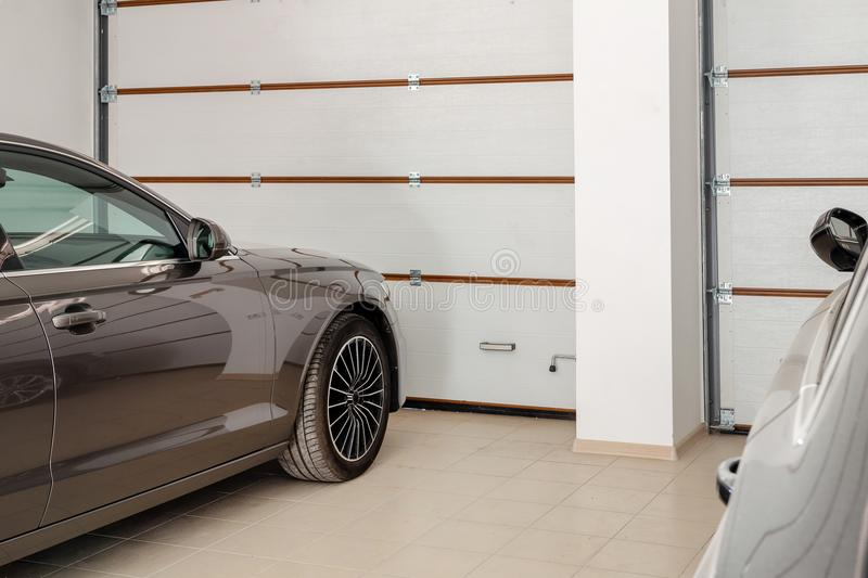 Home garage for two vehicles interior. Clean luxury cars parked at home. Automatic remote control doors. Transport roofed storage.  royalty free stock photos