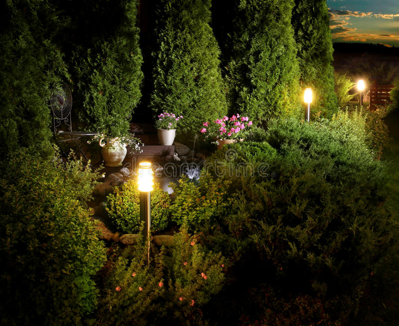 Home garden patio lights on evening dusk. Illuminated home garden patio, plants and fountain on evening dusk royalty free stock photography