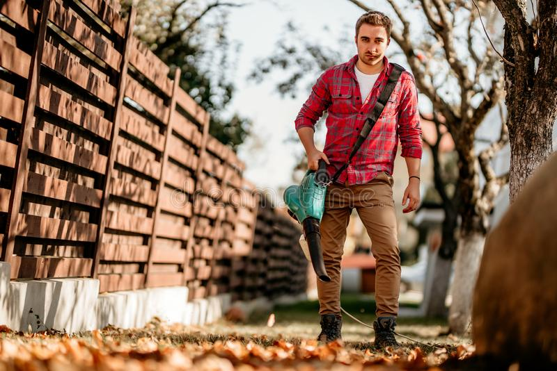 Home gardening details with handsome male working with garden blower stock photo