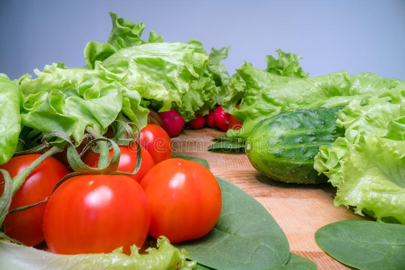 Home grown and harvested vegetables on wooden table background. Fresh lettuce, salad, tomato, radish, spinach and cucumber. stock photo