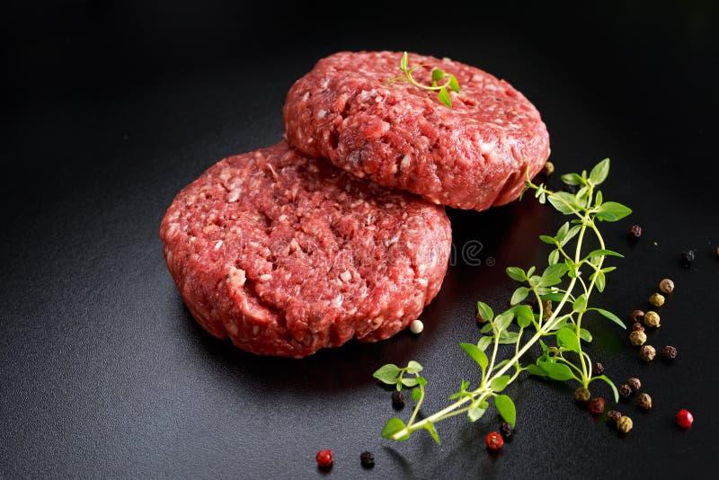 Home HandMade Raw Minced Beef steak burgers on black board stock photography