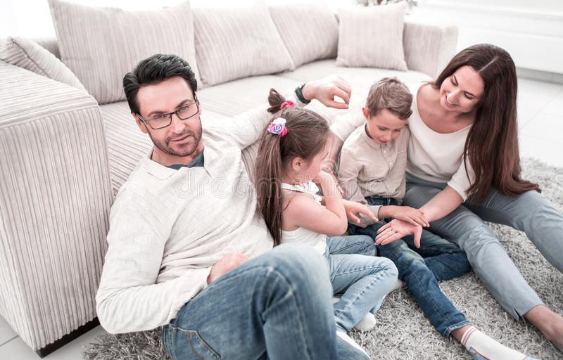 Happy family sitting on the floor, in the living room stock images