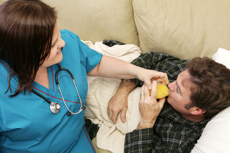 Home Health - Thirsty. A home health nurse helping her patient drink orange juice. Focus on him royalty free stock images