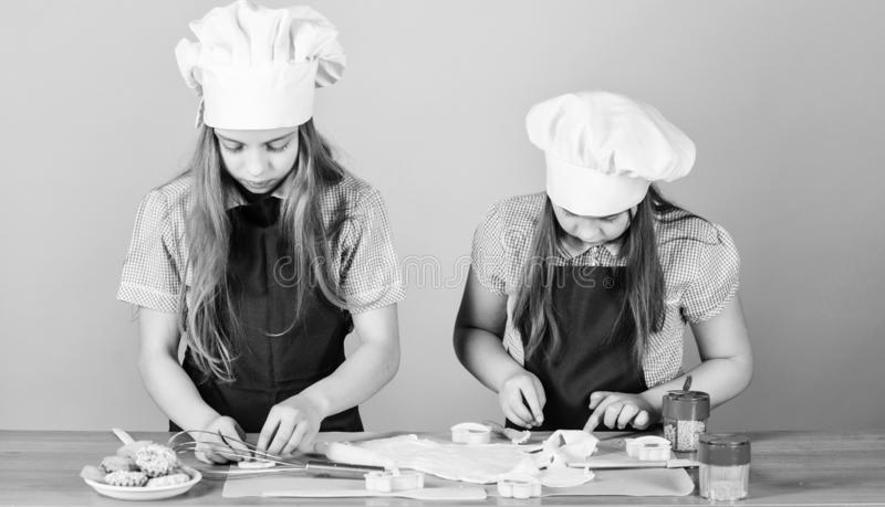 The home of high class baking. Small children taking cooking class together. Little girls preparing cookies in cooking royalty free stock images