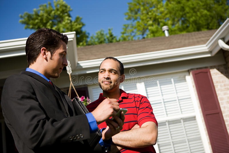 Home: Homeowner Listens to Agent. Extensive series of a Caucasian Real Estate Agent and African-American Couple in front of a home stock images
