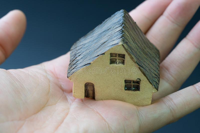 Home / house, real estate or residential concept, miniature ceramic house in real human female hand with dark background stock images