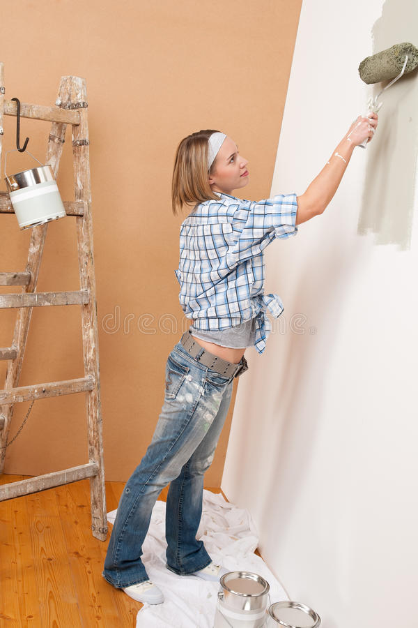 Home improvement: Blond woman painting wall. With paint roller royalty free stock photography
