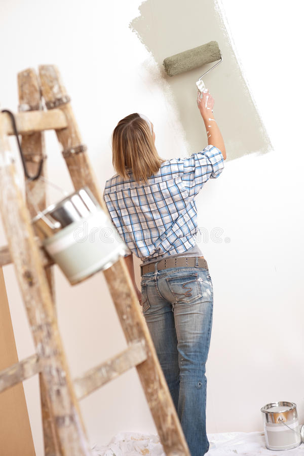 Home improvement: Blond woman painting wall. With paint roller stock image