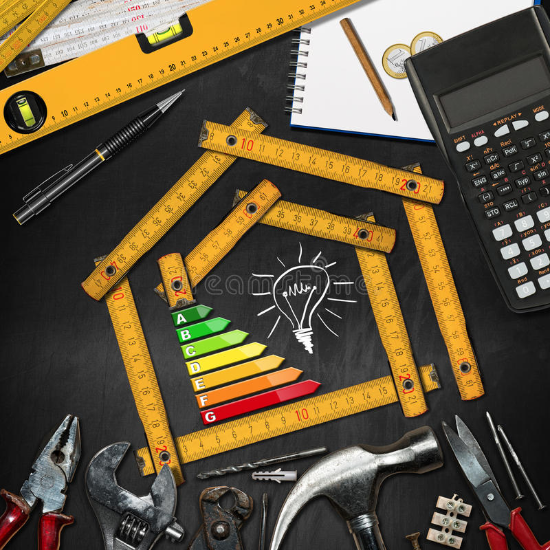 Home Improvement Concept - Energy Efficiency. Home improvement concept - Wooden ruler in the shape of a house with energy efficiency rating on a blackboard with stock photo