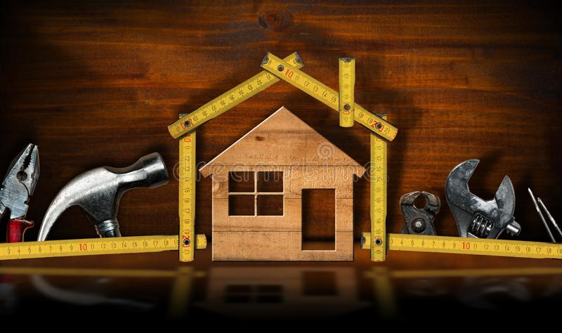 Home Improvement concept - House and work tools. Home improvement concept - Wooden folding ruler in the shape of a house and a wooden model with work tools stock image
