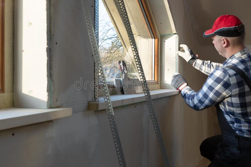 Home improvement handyman installing window in new build attic by using leveler and laser leveler royalty free stock photography