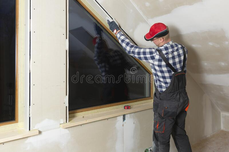 Home improvement handyman installing window in new build attic by using leveler and laser leveler stock photos
