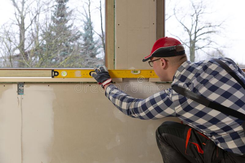 Home improvement handyman installing window sill in new build attic by using leveler and laser leveler royalty free stock photos