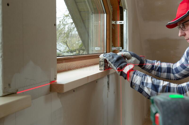 Home improvement handyman installing window sill in new build attic by using leveler and laser leveler stock images