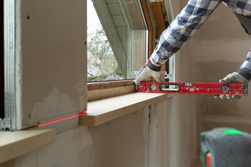 Home improvement handyman installing window sill in new build attic by using leveler and laser leveler stock image