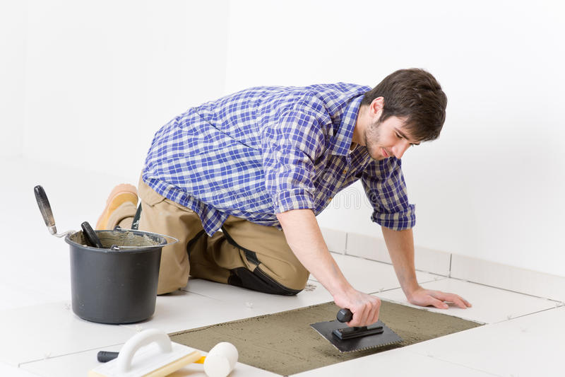 Home improvement - handyman laying tile stock photos