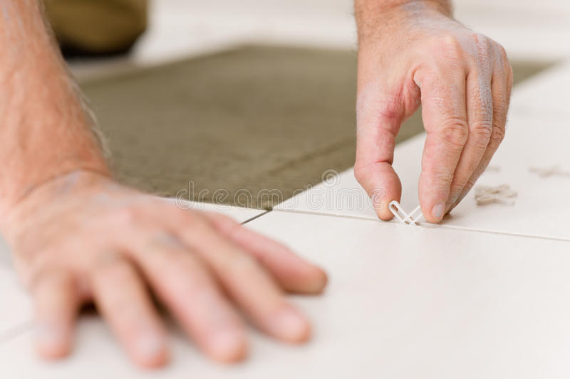 Home improvement - handyman placing tile spacer royalty free stock image