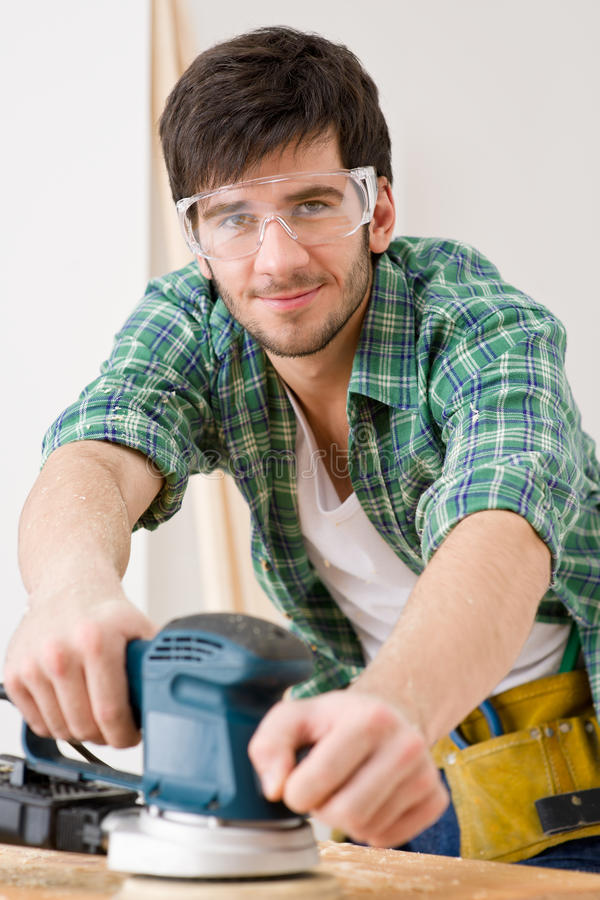 Home Improvement - Handyman Sanding Wooden Floor Royalty Free Stock Photography