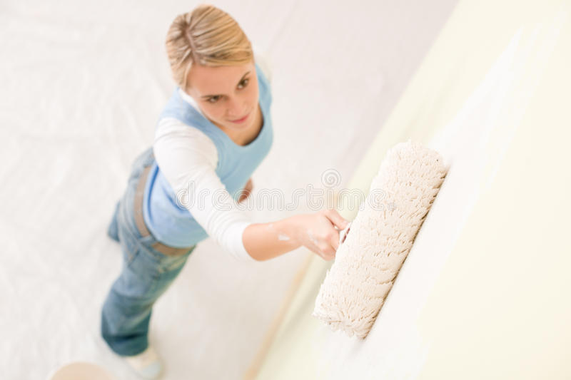 Home improvement - handywoman painting wall. With roller stock photography