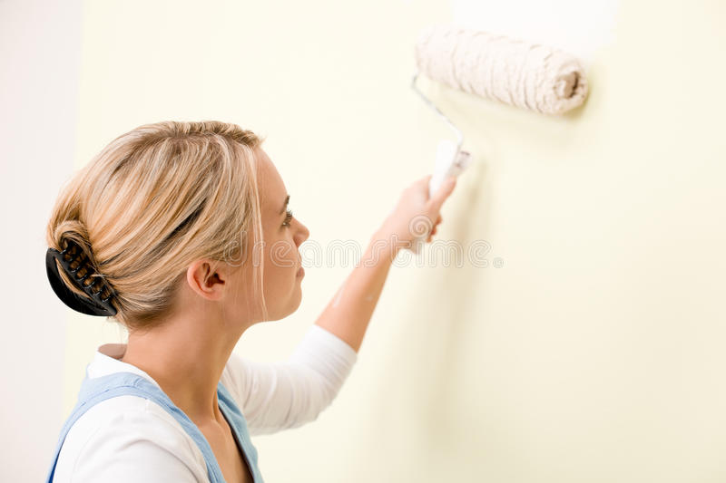 Home improvement - handywoman painting wall. With roller stock photos
