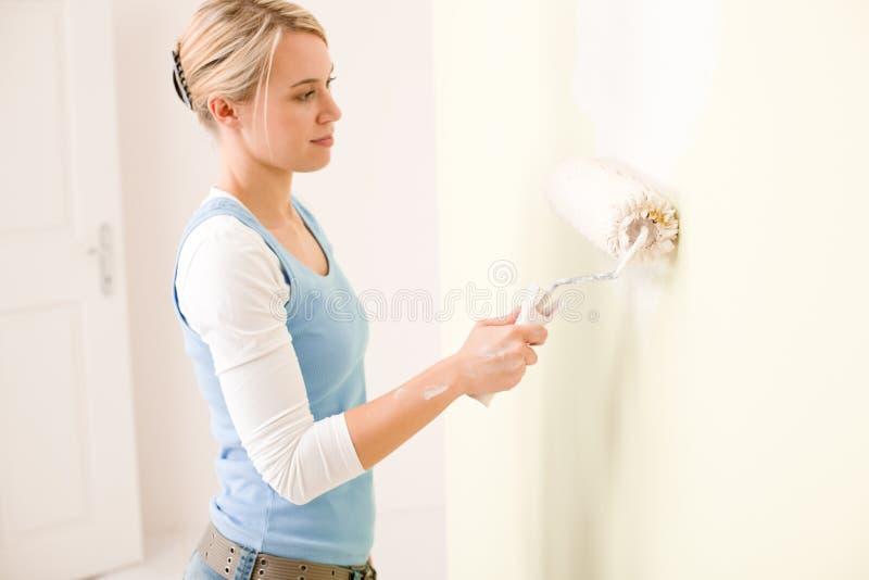 Home improvement - handywoman painting wall stock photo