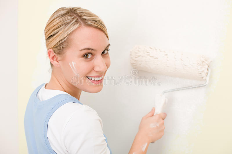 Home improvement - handywoman painting wall. With roller royalty free stock photo