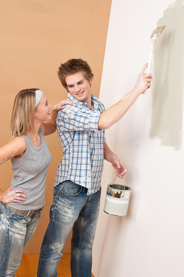 Home improvement: Man painting with paintbrush. Home improvement: Man painting wall with paintbrush holding paint can royalty free stock photography