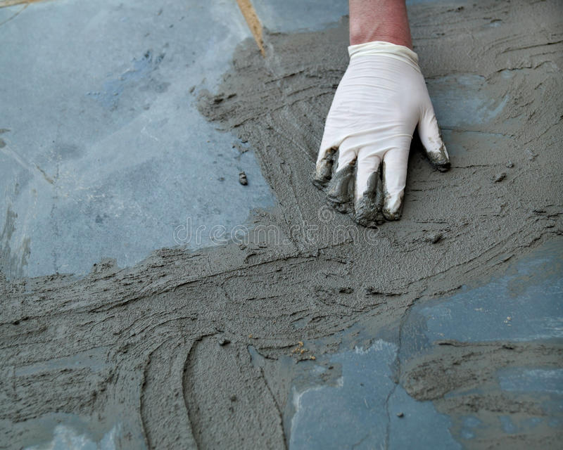 Home Improvement Project. A man working on a home improvement project spreads wet cement on a cracked sidewalk stock images