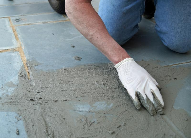 Home Improvement Project. A man working on a home improvement project spreads wet cement to repair a cracked sidewalk stock photos