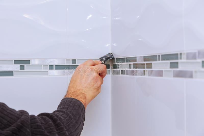 Applying silicone sealant with construction worker fills seam the ceramic tiles on the wall bathroom royalty free stock image