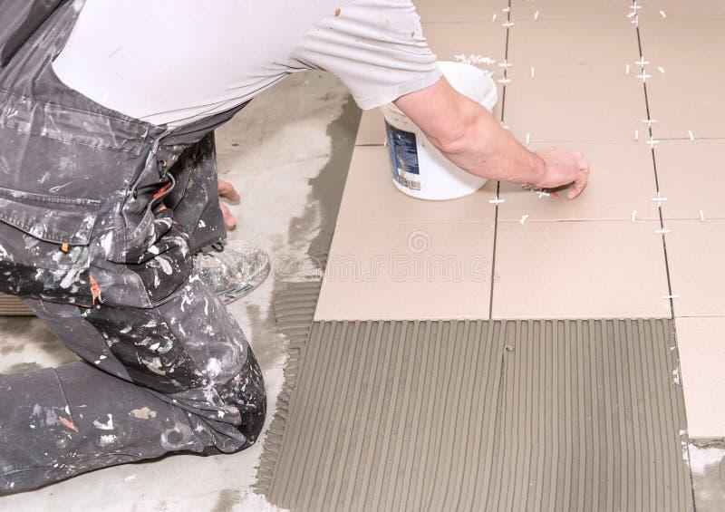 Home improvement, renovation. Construction worker is tiling, ceramic tile. Home improvement, renovation. Construction worker tiler is tiling, ceramic tile floor royalty free stock image